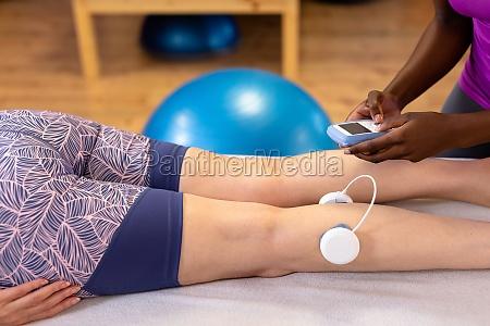physiotherapeutin gibt aktive seniorin im sportzentrum