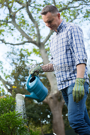 man watering plants with a watering
