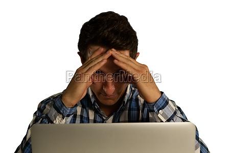 geschaeftsmann benutzt laptop und beruehrt seinen