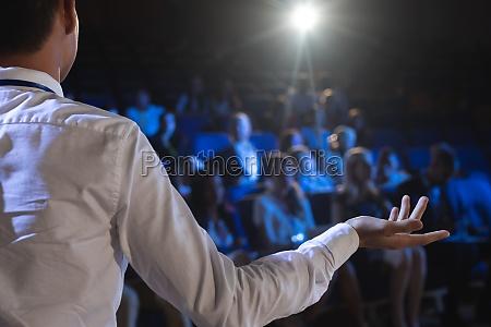 geschaeftsmann bei praesentation vor publikum im