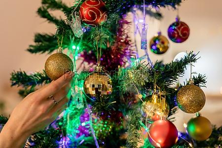 millennial frau schmueckt weihnachtsbaum zu hause