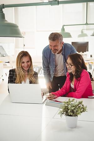 fuehrungskraefte diskutieren ueber laptop am schreibtisch