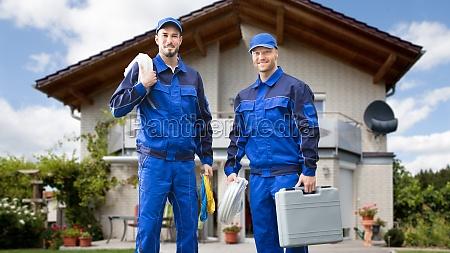 zwei maennliche elektriker vor dem haus
