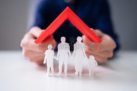 geschaeftsmann schuetzt familienfiguren mit rotem dach