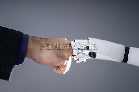 roboter und menschliche hand machen faust
