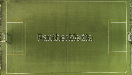 luftaufnahme eines gruenen kunstrasenn fussballplatzes mit