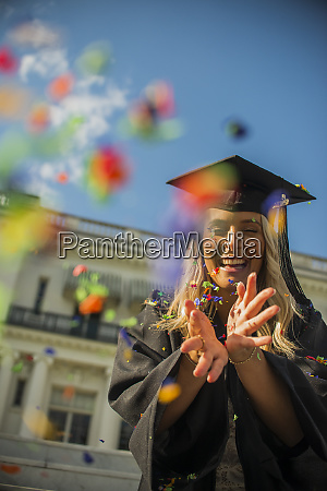 graduating student throwing confetti into air