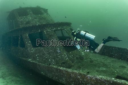 taucher erkunden schiffswrack auf meeresboden