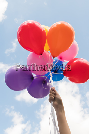 maedchen hand haelt ballons