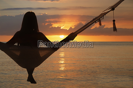 woman sitting in hammock at sunset