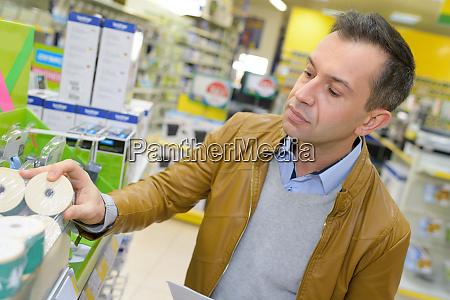 huebscher mann beim einkaufen im supermarkt