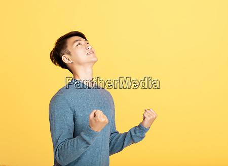 aufgeregter junger mann der nach oben