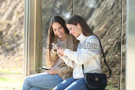 two happy women waiting in a
