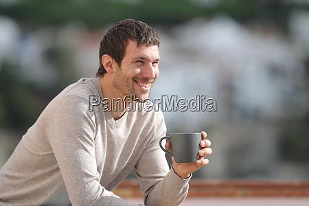 gluecklicher mann haelt kaffeetasse mit blick