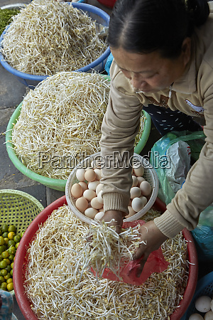woman selling eggs and bean sprouts