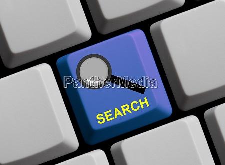 lupensymbol auf blauer computertastatur suchen