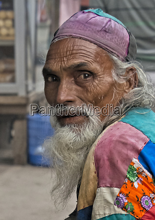 beggar wearing colorful patched robe dhaka