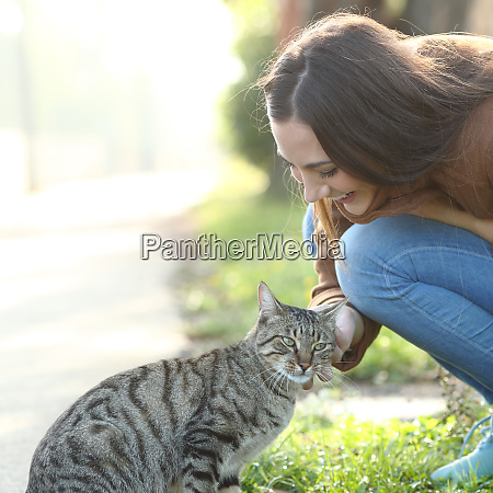 happy woman stroking a cat in