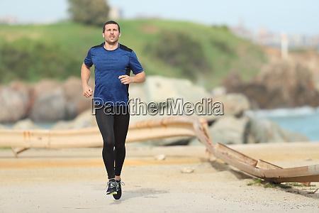 serious runner running on the beach