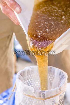 mann giesst honig aus einem grossen