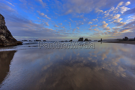 clouds reflect in wet sand at