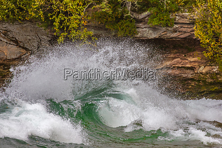 waves curl and crash into cliffs