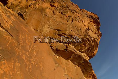 petroglyphs on rock wall at valley