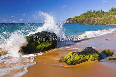 surf crashing on lava rocks at