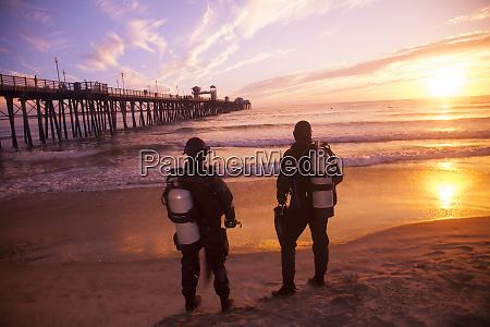 scuba divers in drysuit at sunset