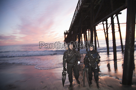 scuba divers in drysuit at sunset