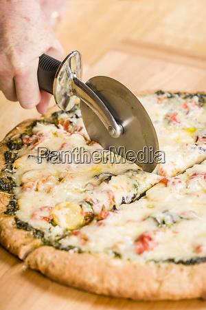frau mit einem pizzaschneider um eine