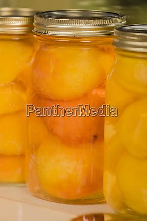 glaeser von pfirsichen mit einem dosendeckel