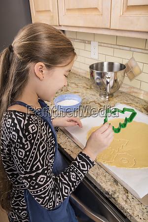 maedchen mit ausstechern um weihnachtszucker kekse