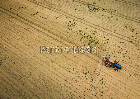 tractor spraying crops in field aerial