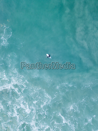 aerial view of lonely surfer floating