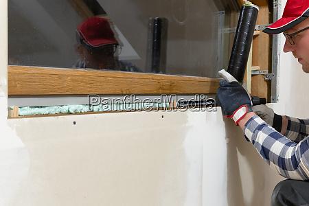 handyman construction man installing pvc window