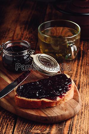 toast mit beerenmarmelade und gruenem tee