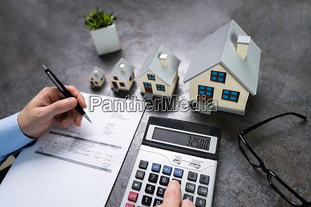 businessman calculating tax by house model