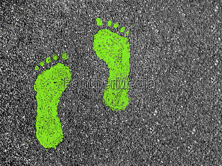 gruene fussabdruecke auf asphalt