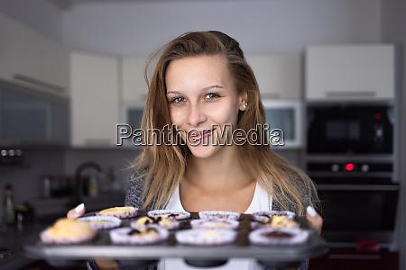 huebsche junge frau backt glutenfreie cupkes