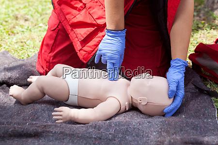 sanitaeter fuehrt cpr auf baby attrappe