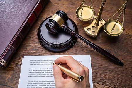 richter schreibt ueber rechtsdokumente am schreibtisch