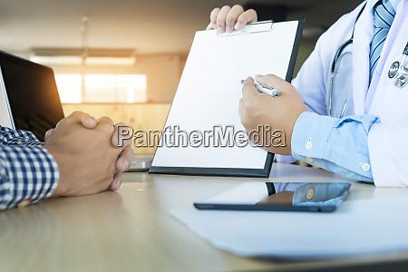 patient hoert einem maennlichen arzt aufmerksam