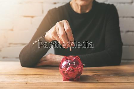 altersvorsorge seniorin steckt muenze in