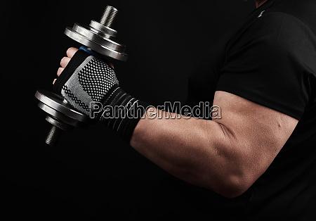 bodybuilder in schwarzer uniform haelt in