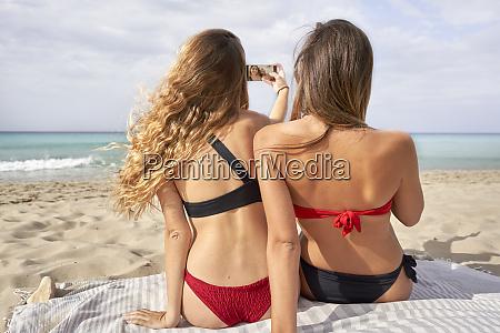 zwei junge frauen sitzen an einem