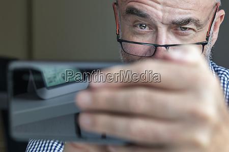 senior mann mit smartphone zu hause