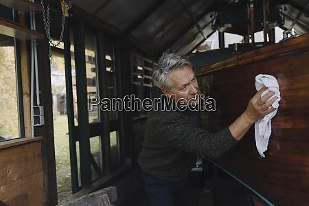 senior mann reinigung holzboot in einem