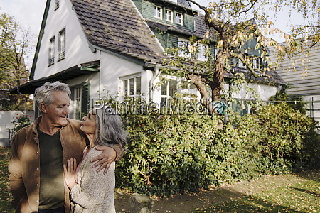seniorenpaar im garten ihres hauses im