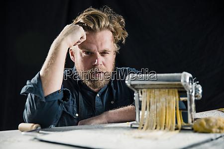 hobbykoch macht frische tagliatelle mit nudelmaschine